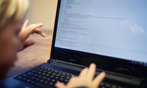 K-12 student at computer keyboard